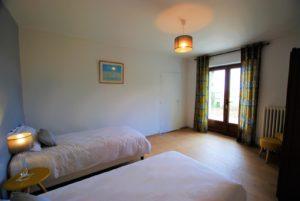 La chambre du rez-de-chaussée et ses deux lits simples