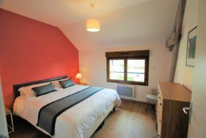 La chambre orange et son grand lit double